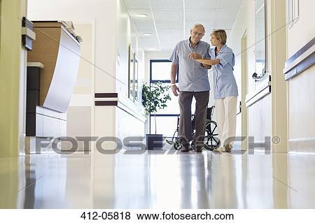 Nurse Helping Patient Walk In Hospital Hallway