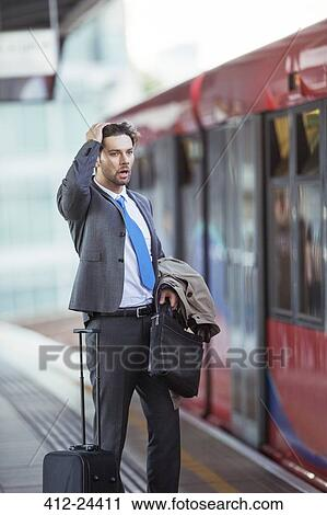 Frustrated businessman missing train in train station Stock Image