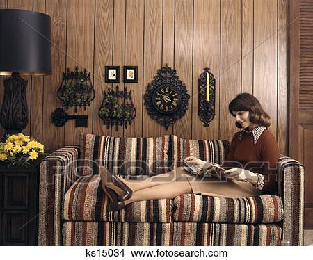 stock photo of 1970 1970s retro woman sofa couch wood paneling clock