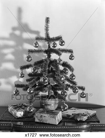 Small Silver Christmas Tree.Small Christmas Tree Decorated With Silver Balls Sitting On Table With Wrapped Gifts Around Stock Photo