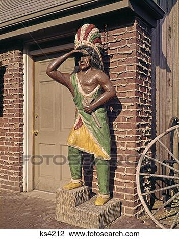 Wooden Statue Of Cigar Store Indian By Brick Building Keeping Vigil Alert Guard Carved Carving Chief Vintage Retro Stock Image