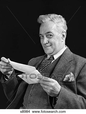 stock photo of 1940 1940s man in suit holding opened mail lettet