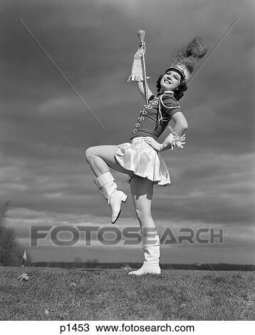 891f5608e39a5c 1940s, femme, dans, majorette, commandant tambour, bande, uniforme, bâton,  fringed, gants, chapeau, plume, plume, bottes, courte jupe, jambe, ...