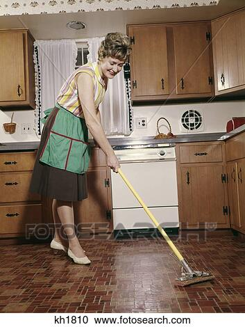 Stock Photography of 1960S Woman In Apron Cleaning Kitchen Floor ...