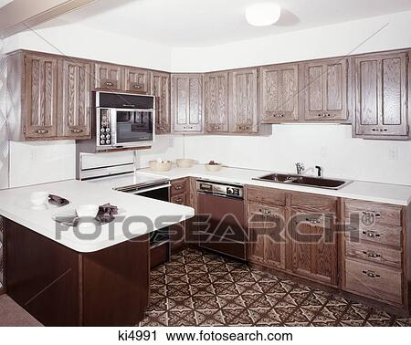1970s kitchen with dark wooden cabinets and a microwave oven ...