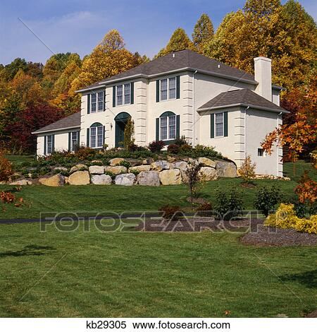 White House With Gray Shutters And Stone Wall In Front Yard Stock Photography