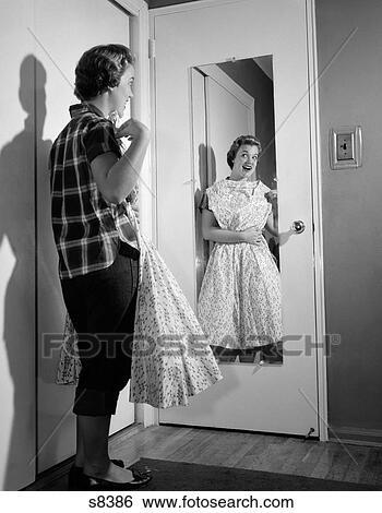 Stock afbeeldingen 1950s tiener meisje in jeans vasthouden galajurk op om te borst - Foto van tiener slaapkamer ...