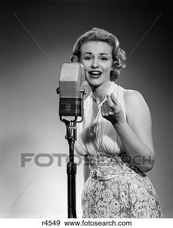 1950S Portrait Woman Entertainer Singing Into A Microphone Studio Looking  At Camera Stock Photo