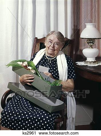 best loved cb820 ad651 1960S Smiling Senior Elderly Old Lady Grandma Granny Sitting In Rocking  Chair Looking At Camera Holding Box Of Flowers Stock Image