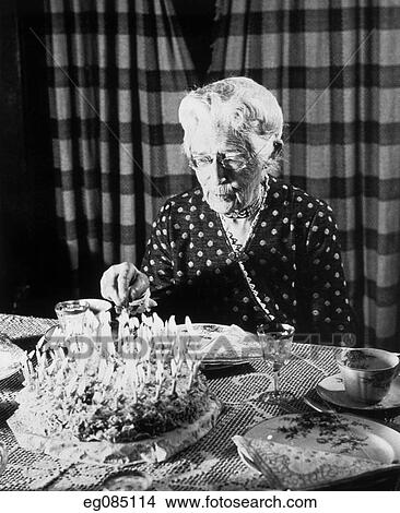 1940S 1950S Elderly Senior Woman About To Cut Birthday Cake Covered In Candles