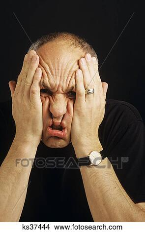 Portrait Of Stressed Man Scrunching Up Face With Hands ...