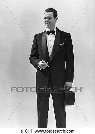 68c08fba567e9 Stock Image - 1950S Portrait Smiling Man Wearing Tuxedo Holding Cigarette  And Fedora Hat . Fotosearch