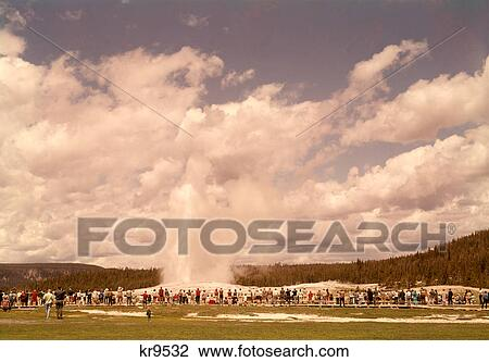 1960s CROWD WATCHING OLD FAITHFUL GEYSER YELLOWSTONE NATIONAL PARK PARKS  WYOMING USA Stock Image