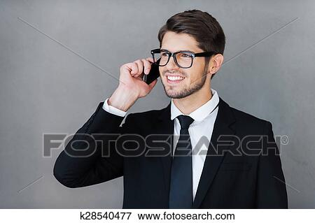 c578fe1ac276 Good business talk. Happy young businessman talking on the mobile phone and  looking away while standing against grey background