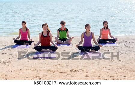 yoga class at sea beach in sunny day group of people