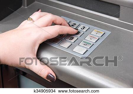 Woman's hand entering PIN code on ATM machine Picture