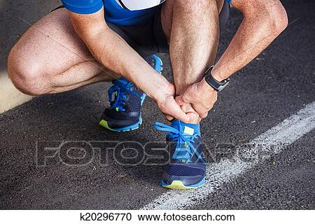 Broken twisted ankle - running sport injury  Male runner touchin Stock Image