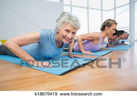 group doing cobra pose in row at yoga class stock photo