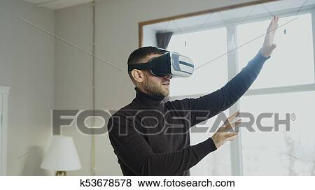 753685de4d1f Picture - Excited man with virtual reality headset playing 360 video game  at home. Fotosearch