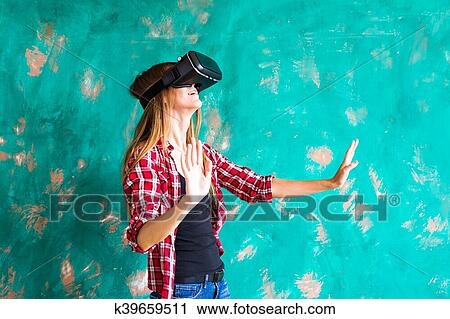 b3944d33c550 Smile happy woman getting experience using VR-headset glasses of virtual  reality at home much gesticulating hands.