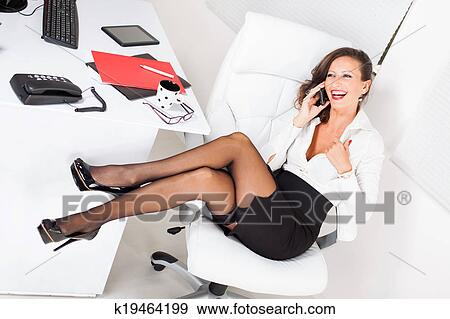 Sexy Business Woman Sitting On Office Chair And Talking On Mobile Phone