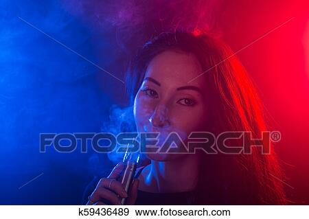 Portrait Of Girl In Colored Neon Smoke With Vape Or Electronic Cigarette Stock Photo K59436489 Fotosearch