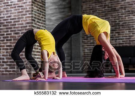 kids yoga female teacher training a child girl standing in