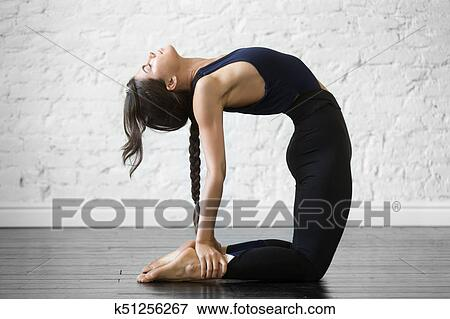 young attractive woman in ustrasana pose studio