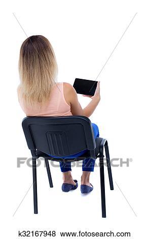 Rückenansicht Von Frau Sitzen Stuhl Und Aussehen Dass Schirm Von Dass Tablet Stock Foto