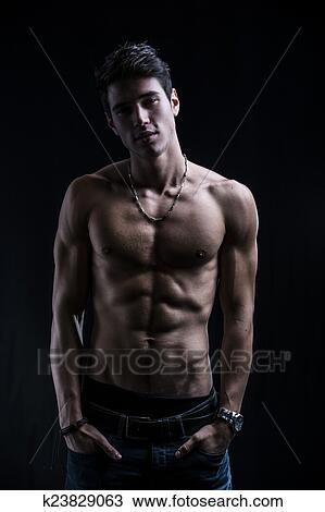 e173210f4 Handsome muscular shirtless young man standing confident with hands in his  pockets