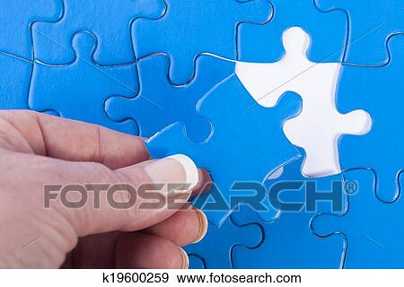 Close Up Of Womans Hand Placing Missing Piece In Jigsaw Puzzle Signifying Problem Solving And Decision Making
