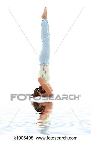salamba sirsasana supported headstand on white sand stock