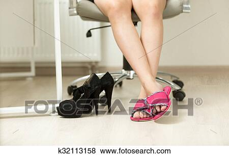Picture   Closeup Of Businesswomen Feet In Slippers Under Office Table.  Fotosearch   Search Stock