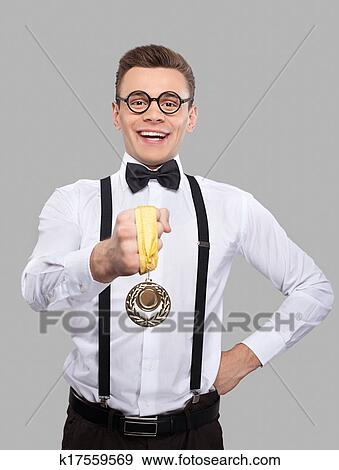 904dbb391ca7 Cheerful young man in bow tie and suspenders showing a gold medal to camera  and smiling while standing against grey background Stock Photo