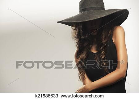 ca7f5b066db Beautiful young woman with red lips wearing summer black hat with large brim