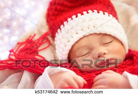 7363d575c9b4a Portrait of a sweet newborn baby wearing red knitted Santa hat and scarf