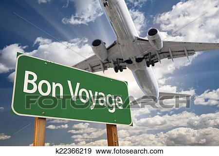 stock photograph of bon voyage green road sign and airplane above