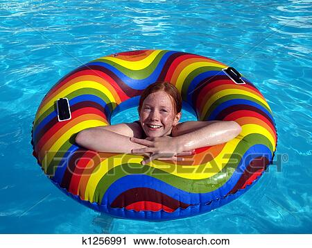 Girl in a swimming pool with rubber ring Stock Image