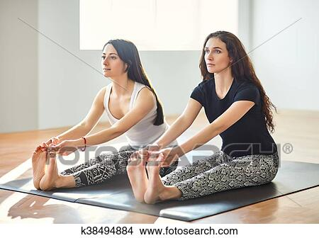 two young women doing yoga asana holding toes with concave