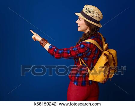 Turista, mujer, contra, fondo azul, el señalar en, algo Colección de imágen