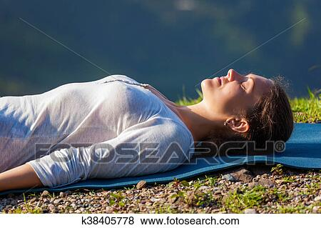 mulher relaxa em ioga asana savasana ao ar livre