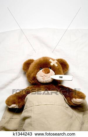 Stock photo of sick teddy bear k1344243 search stock images a very sick teddy bear laying in his bed thecheapjerseys Image collections