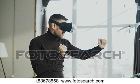 acebb42c45e5 Excited man with virtual reality headset dancing and play 360 video game at  home