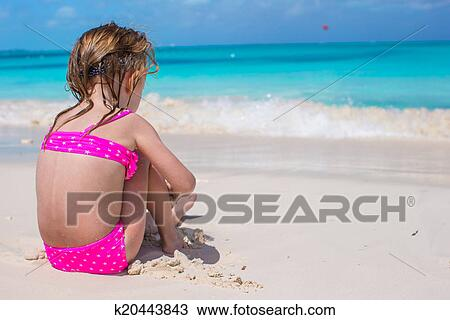 Little girl in bikini rear view Adorable little girl in swimsuit at tropical beach