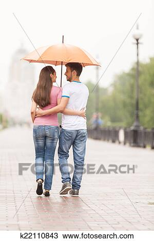 stock photo of view of couple back under umbrella walking man