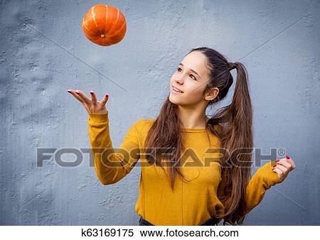 Young girl throwing up orange pumpkin on grunge background ...