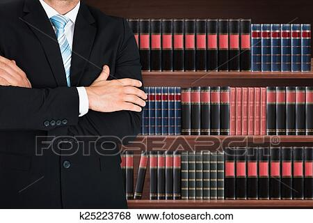 Close Up Of Male Lawyer With Arm Crossed Standing In Front Book Shelf