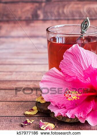 Glass Cup With Red Tea Pink Hibiscus Flower On Dark Wood Background