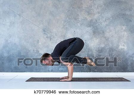 sporty young man working out doing handstand yoga asana