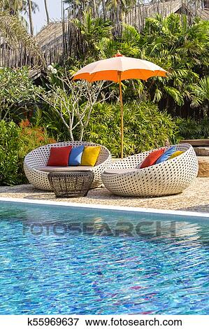 Tropical beach with swimming pool, coconuts palm trees, rattan daybeds and  umbrella near sea, Thailand Stock Photo